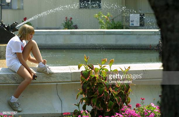 Kristen Maslowski visiting from Chicago sits on the fountain of Bartholdi Park