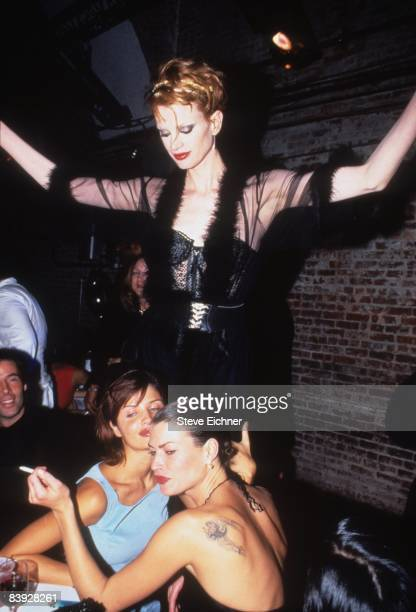 Kristen McMenamy stands above Helena Christiansen and Carre Otis at a table in The Tunnel nightclub during the Venus of Fashion Awards 1994