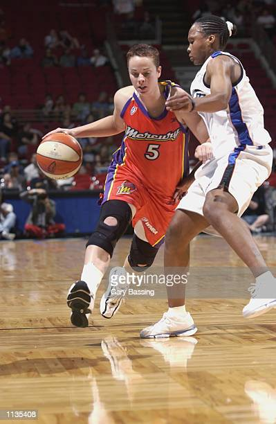 Kristen Veal of the Phoenix Mercury drives past Elaine Powell of the Orlando Miracle in the game on July 6 2002 at TD Waterhouse Centre in Orlando...