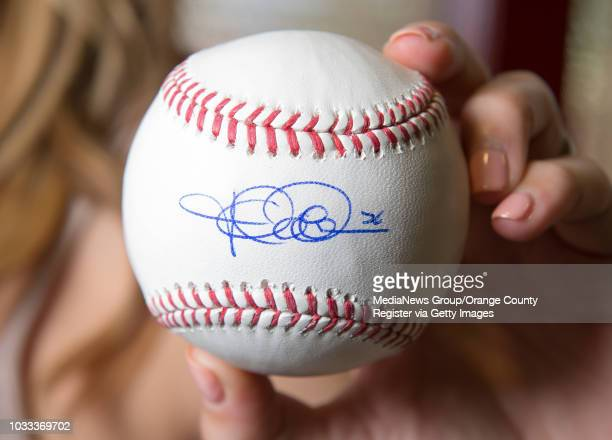 Kristen Weaver displays a baseball signed by her husband Jered Weaver of the Angels The signed baseballs will be part a charity fundraiser on...