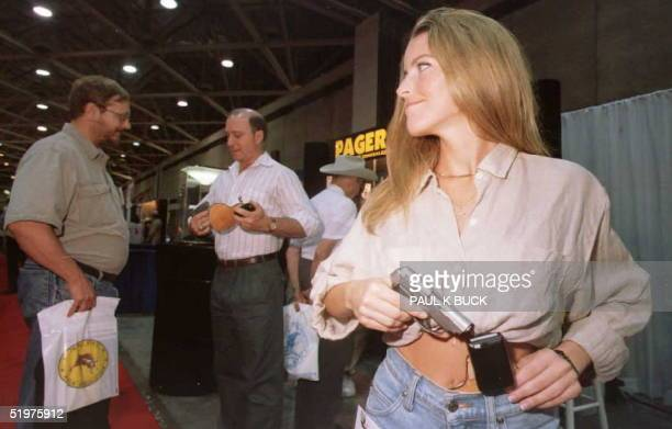 Kristen Whitehurst demonstrates a holster disguised as a pager for carrying a concealed handgun during the National Rifle Association's 125th...