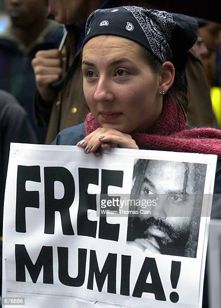 Kristen who declined to give her last name leans on her FREE MUMIA sign as she listens to a speaker at a demonstration in support of convicted cop...