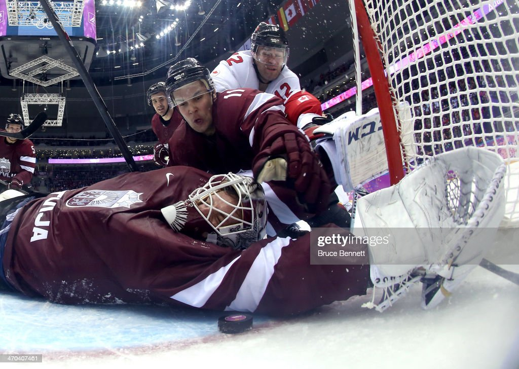 Kristers Gudlevskis #50 of Latvia makes a save against Canada during the third period with the help of teammate Kristaps Sotnieks #11 during the Men's Ice Hockey Quarterfinal Playoff on Day 12 of the 2014 Sochi Winter Olympics at Bolshoy Ice Dome on February 19, 2014 in Sochi, Russia.