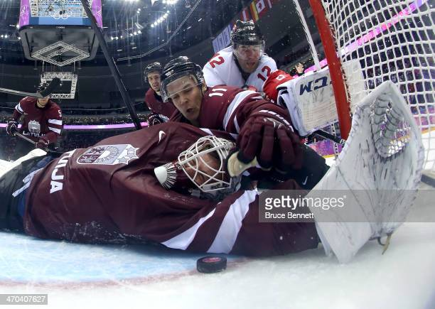 Kristers Gudlevskis of Latvia makes a save against Canada during the third period with the help of teammate Kristaps Sotnieks during the Men's Ice...