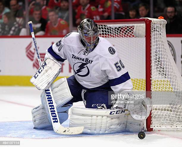 Kristers Gudlevskis of the Tampa Bay Lightning knocks the puck away against the Chicago Blackhawks at the United Center on October 24 2015 in Chicago...
