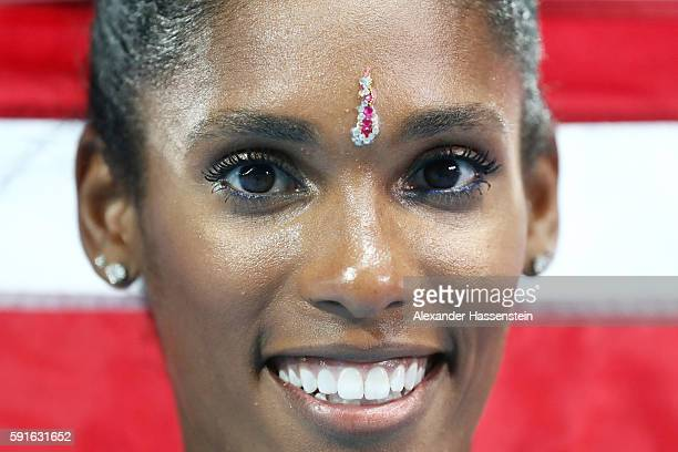 Kristi Castlin of the United States poses with the American flag after winning the bronze medal in the Women's 100m Hurdles Final on Day 12 of the...