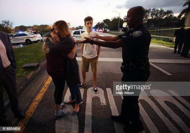 Kristi Gilroy hugs a young woman as a police officer tries to clear a closed road at a police check point near the Marjory Stoneman Douglas High...