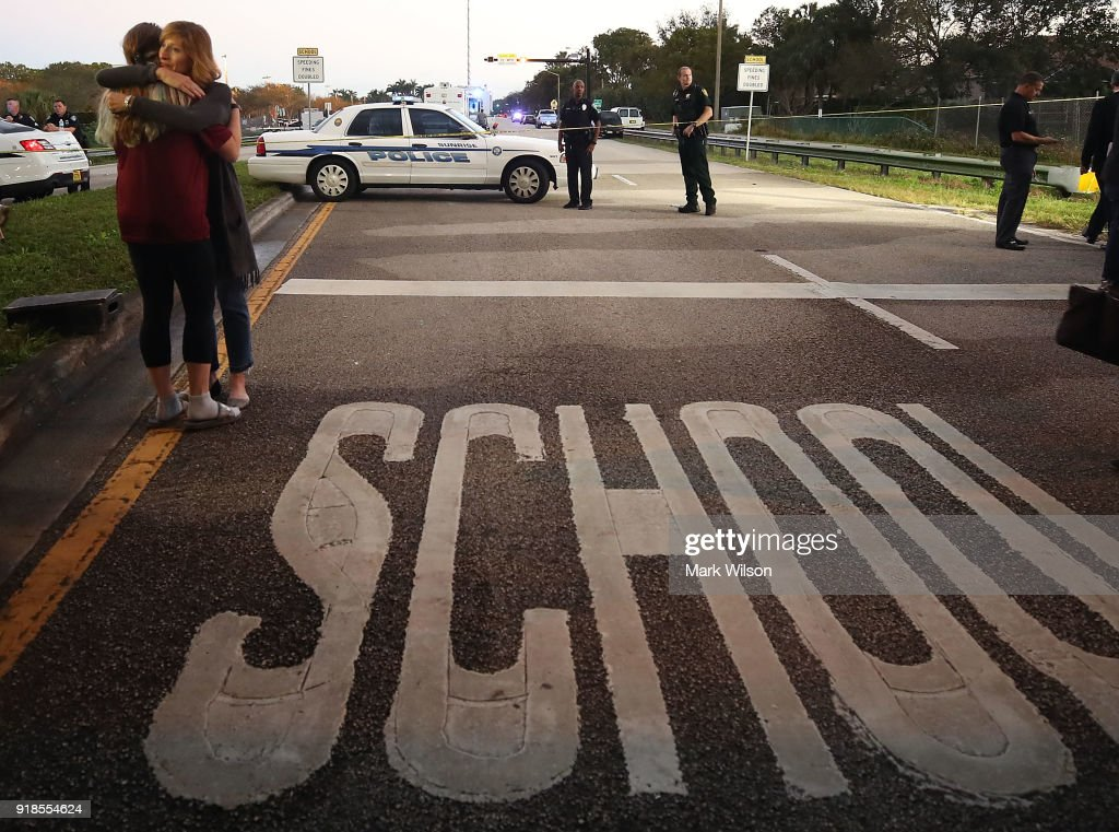 Kristi Gilroy (R), hugs a young woman at a police check point near the Marjory Stoneman Douglas High School where 17 people were killed by a gunman yesterday, on February 15, 2018 in Parkland, Florida. Police arrested the suspect after a short manhunt, and have identified him as 19-year-old former student Nikolas Cruz.