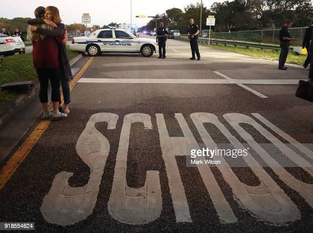 Kristi Gilroy hugs a young woman at a police check point near the Marjory Stoneman Douglas High School where 17 people were killed by a gunman...
