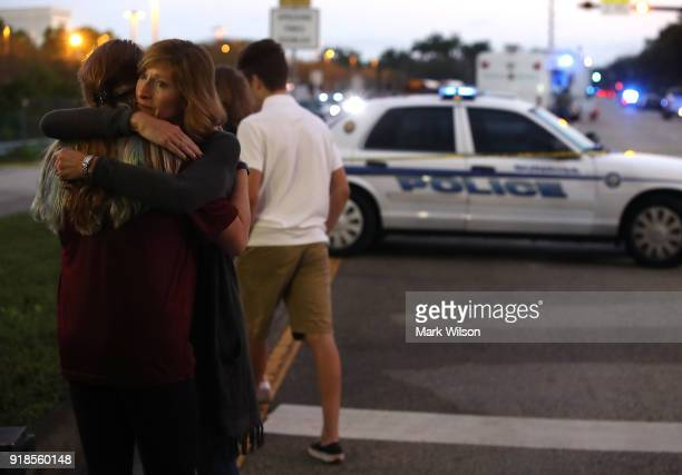 Kristi Gilroy hugs a young woman at a police check point near the Marjory Stoneman Douglas High School where 17 people yesterday were killed by a...