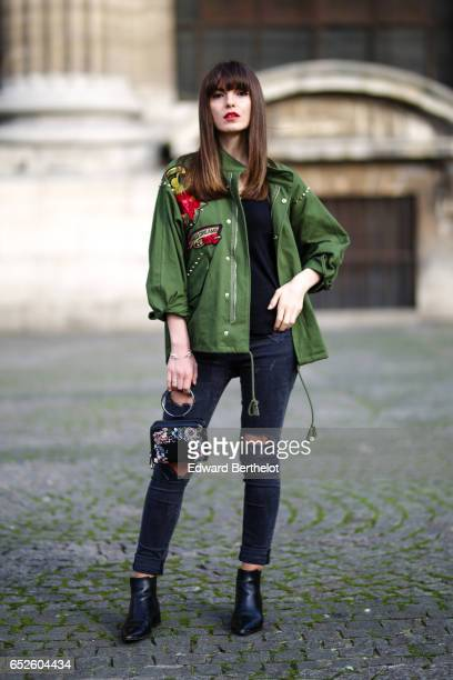 Kristi Gogsadze, fashion blogger La Georgienne, wears Zara black denim jeans cropped and ripped trousers, a Zara black top, a Zara green bomber...