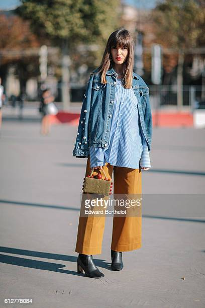 Kristi Gogsadze is wearing COS pants a Zara shirt Charles Keith boots a Tonya Hawkes clutch and a blue denim jacket outside the Chanel show during...
