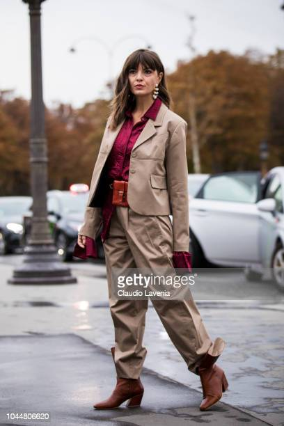 Kristi Gogsadze wearing a pink shirt beige blazer beige pants orange fanny pack and tan boots is seen before the Chanel show on October 2 2018 in...