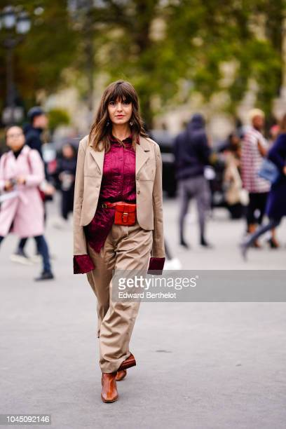 Kristi Gogsadze wears a beige blazer jacket a purple shirt a red belt bag beige pants brown leather boots outside Chanel during Paris Fashion Week...