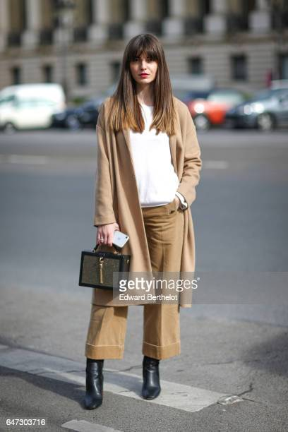 Kristi Gogsadze wears a beige jacket a white top beige pants and black boots outside the Manish Arora show during Paris Fashion Week Womenswear...