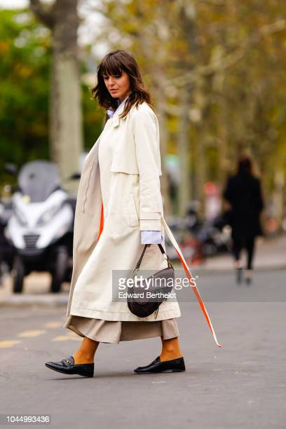 Kristi Gogsadze wears a white trench coat, a Dior Saddle bag, during Paris Fashion Week Womenswear Spring/Summer 2019, on October 2, 2018 in Paris,...