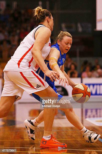 Kristi Harrower of the Spirit drives to the basket past Suzy Batkovic of the Fire during the WNBL Grand Final match between Bendigo Spirit and...