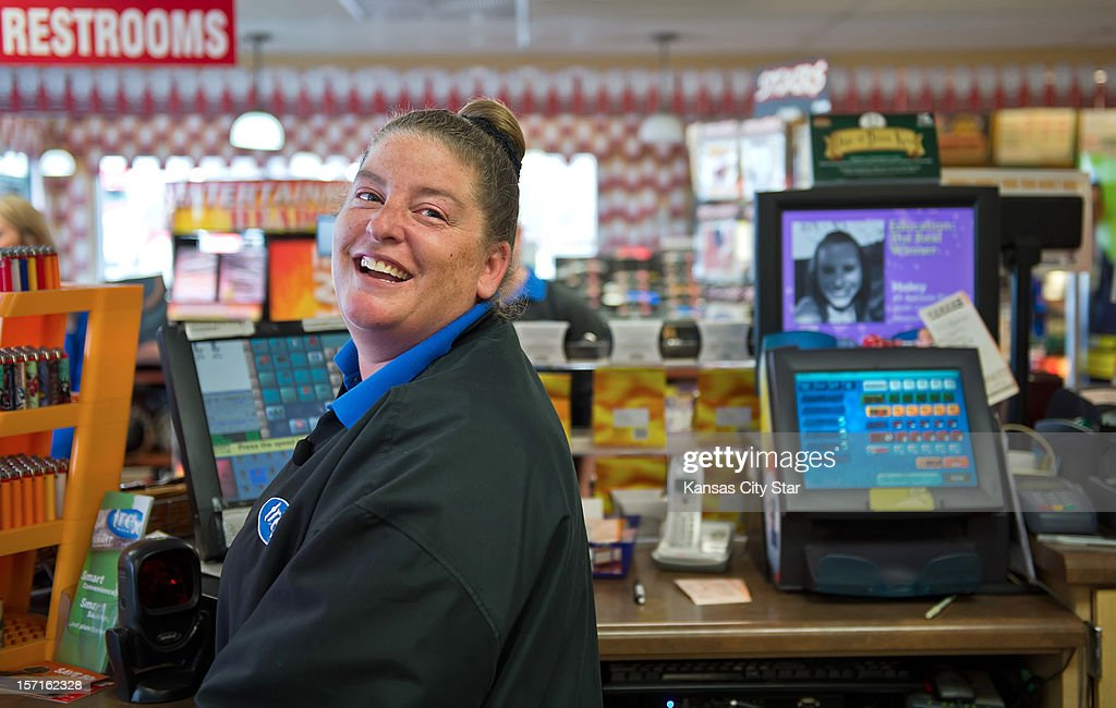 Kristi Williams, a sales associate at the Trex Mart gas station in Dearborn, Missouri, smiles next to the lottery machine at right that was used to sell one of the winning lottery tickets for the Powerball jackpot inside the gas station. The location of the winning tickets was announced on Thursday, November 29, 2012.