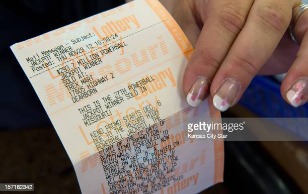 Kristi Williams a sales associate at the Trex Mart in Dearborn Missouri holds a paper Powerball receipt Thursday November 29 stating one of the...