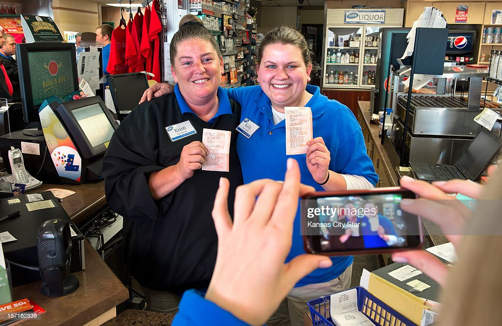Kristi Williams, left, and Kelly Blount, both sales associates at the Trex Mart in Dearborn, Missouri, pose for a cell phone photograph, Thursday, November 29, 2012, holding a paper Powerball receipt stating one of the national winners purchased a winning lottery ticket inside the gas station. The location of the winning tickets was announced on Thursday.