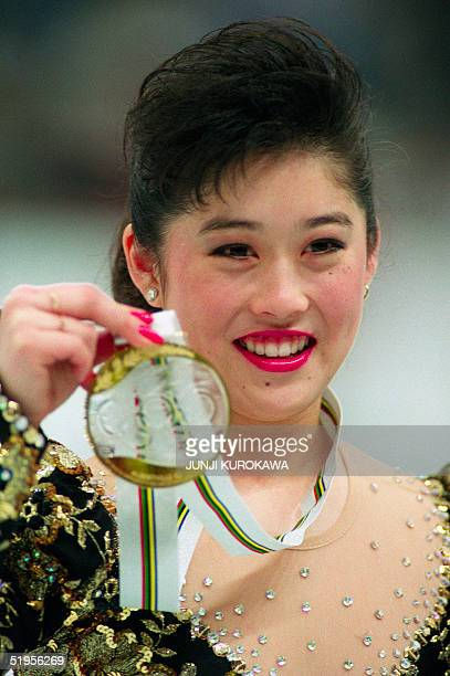 Kristi Yamaguchi from the United States smiles as she displays her gold medal on the podium of the women's figure skating event at the Winter Olympic...