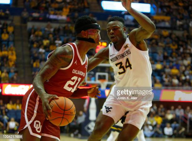 Kristian Doolittle of the Oklahoma Sooners drives the baseline against Oscar Tshiebwe of the West Virginia Mountaineers at the WVU Coliseum on...