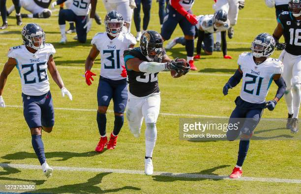 Kristian Fulton, Kevin Byard, and Malcolm Butler of the Tennessee Titans watch as James Robinson of the Jacksonville Jaguars scores a touchdown...