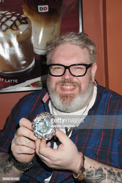 Kristian Nairn AKA Hodor from Game of Thrones holds the door and serves dark roast coffee to welcome winter at Dunkin' Donuts on December 21 2017 in...