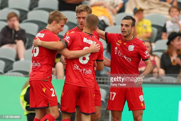 Kristian Opseth of Adelaide United celebrates a goal with team mates during the round 6 A-League match between the Central Coast Mariners and...