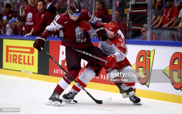 Kristians Rubins of Latvia and Nichlas Hardt of Denmark battle for the puck during the 2018 IIHF Ice Hockey World Championship Group B game between...