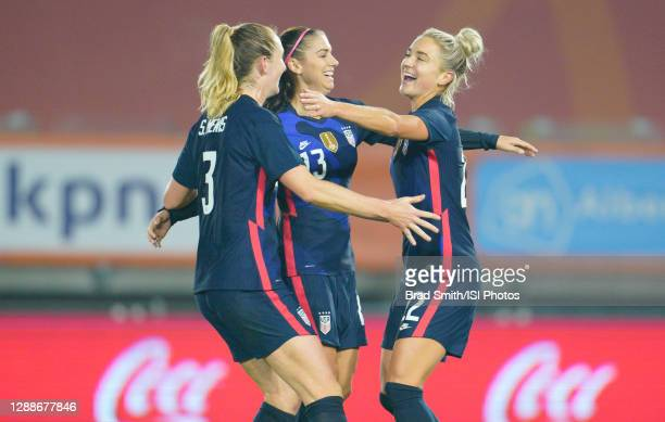 Kristie Mewis of the United States scores a goal and celebrates with her sister Samantha Mewis and teammate Alex Morgan during a game between...