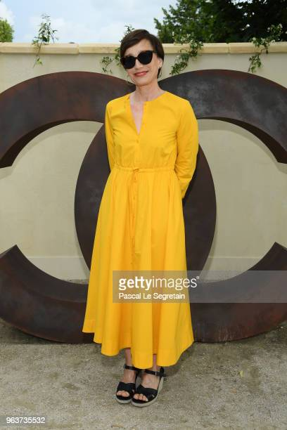 Kristin Scott Thomas poses at a photocall prior the Chanel Opening Party for the Exhibition 'Dans les Champs de Chanel' at Jardin des Tuileries on...