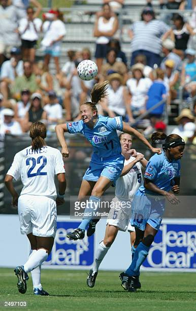 Kristin Warren of the Atlanta Beat heads the ball over the defense Steffi Jones and Carrie Moore of Washington Freedom during the Founders Cup...