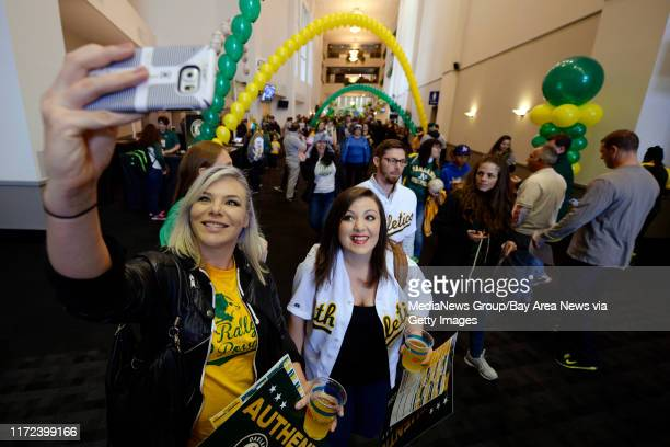 Kristina Banks of San Francisco holds her phone up high as she attempts to take a selfie with friend Katie Emry of Concord as Oakland Athletics' Eric...