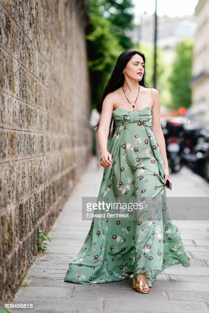 Kristina Bazan wears a green off-shoulder flower print dress, a necklace, and shoes, outside the Valentino show, during Paris Fashion Week - Haute...