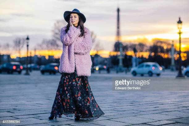 Kristina Castillo fashion and life style blogger wears a SHE pink fur coat Celine black boots a Mango black dress with floral print a Mango hat and a...