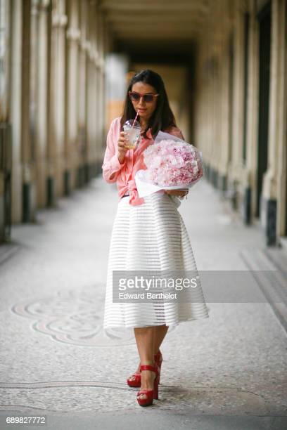 Kristina Castillo wears Furla sunglasses a Benetton sleeveless white floral print top a Maje pink shirt Gucci red heels shoes and a white lace skirt...