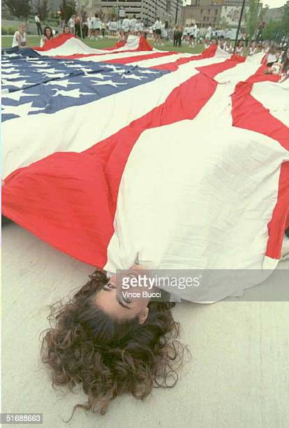 Kristina Georgelas bundles up under a huge American flag 16 June before the start of a parade celebrating Salt Lake City being chosen to host the...