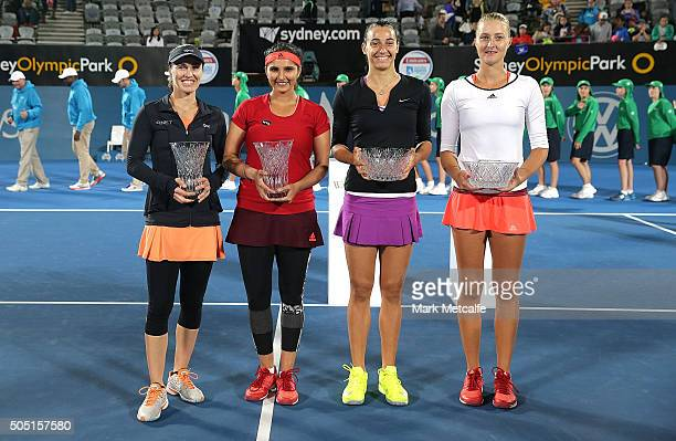 Kristina Mladenovic and Caroline Garcia of France pose with the winners trophy and Sania Mirza of India and Martina Hingis of Switzerland the runners...