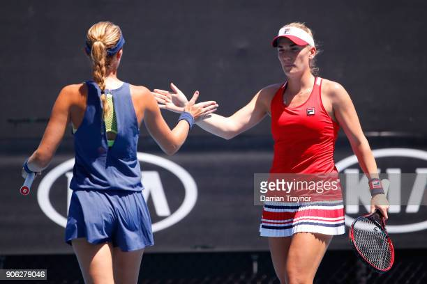 Kristina Mladenovic and Timea Babos of Hungary talk tactics in their first round women's doubles match against Xenia Knoll of Switzerland and Natela...