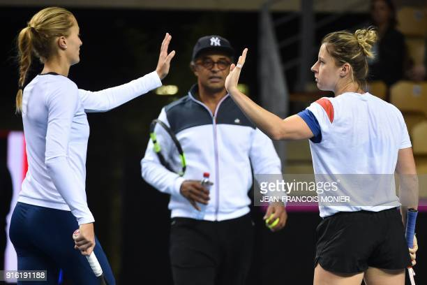 Kristina Mladenovic from France and Pauline Parmentier from France congratulate each other next to France's captain Yannick Noah during a training...