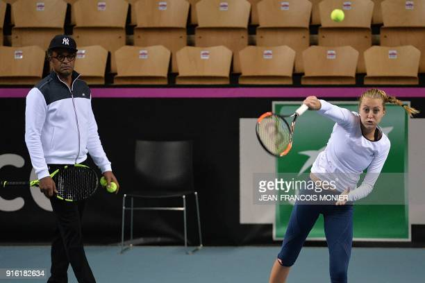Kristina Mladenovic from France returns the ball next to captain of the French team Yannick Noah during a training session prior to the Fed Cup World...