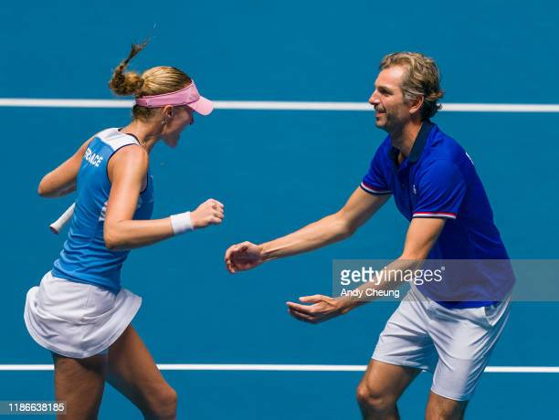 Kristina Mladenovic of France celebrates with French Captain Julien Benneteau after winning the Day 2 match against Ashleigh Barty of Australia in...