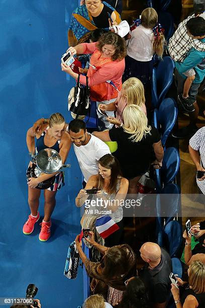 Kristina Mladenovic of France holds the Hopman Trophy while posing for selfies after defeating Coco Vandeweghe and Jack Sock of the United States in...