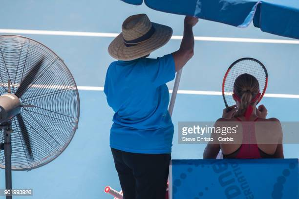 Kristina Mladenovic of France sits under a umberella in the Sydney heat during day one of the 2018 Sydney International at Sydney Olympic Park Tennis...