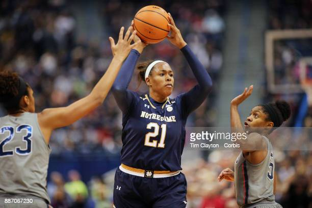 Kristina Nelson of the Notre Dame Fighting Irish defended by Azura Stevens of the Connecticut Huskies and Crystal Dangerfield of the Connecticut...