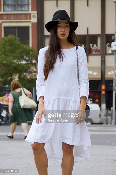 Kristina Petrick wearing white linen Sauths dress with pleats and three quarter length sleeves black fedora hat by Brixton YSL black leather quilted...