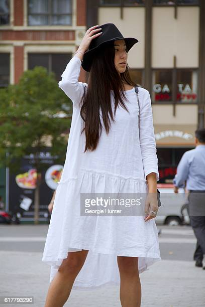 Kristina Petrick wearing white linen Sauths dress with pleats and three quarter length sleeves black fedora hat by Brixton Wyeth brown oversized...
