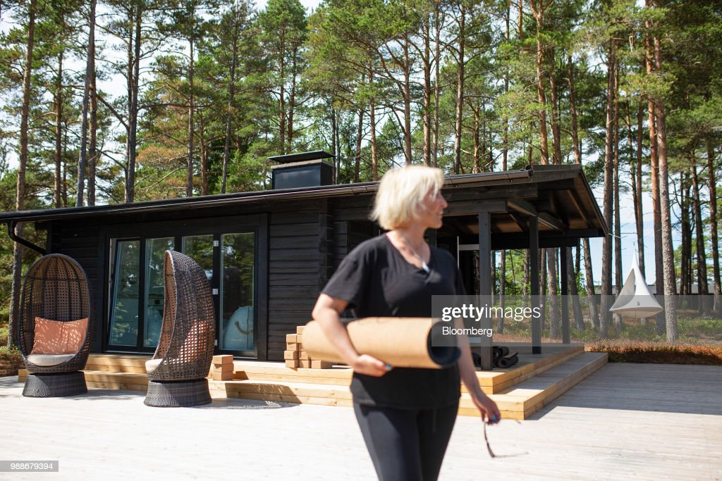 Kristina Roth, founder of the SuperShe network, carries a yoga mat in front of a guest cabin on SuperShe island near Raasepori, Finland, on Wednesday, June 27, 2018.v The price of experimental networking on the island that has banned men, and only accepts heavily vetted women, is 4,000 euros, or $4,600. The package includes self-help tools that can lead participants down a different career path, as well as cognitive training to expel any negative thoughts. Photographer: Heli Blafield/Bloomberg via Getty Images