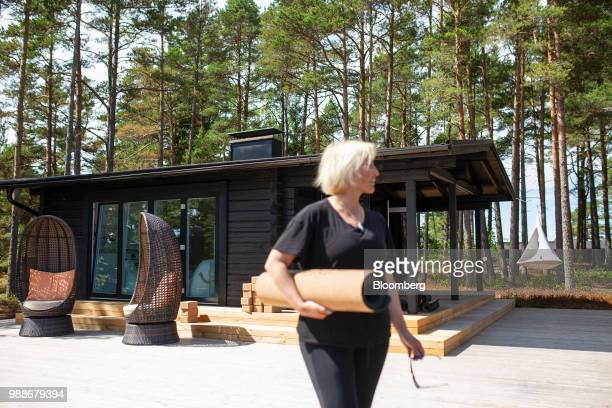 Kristina Roth, founder of the SuperShe network, carries a yoga mat in front of a guest cabin on SuperShe island near Raasepori, Finland, on...